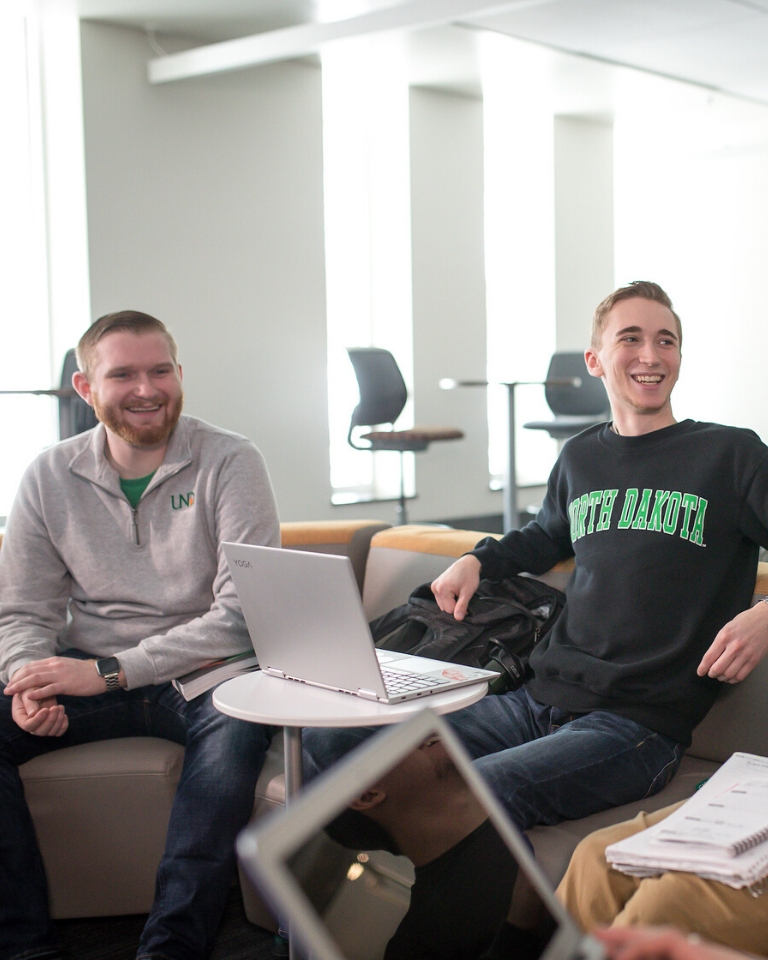 Students smiling with computer