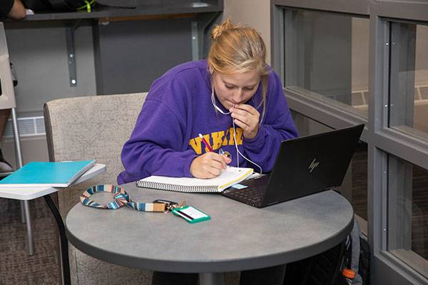 student with headphones on laptop